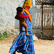 A Rajasthani woman with a burqua covering her face walks toard the village well with her young son on her hip. In Rajasthani tradition she carries her ceramic water pot balanced on her head.