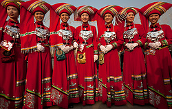 Stewardesses in ethnic minority costumes pose for photos before the opening session of the National Peoples Congress (NPC) outside the Great Hall of the People in Beijing, China, on 05 March 2011. The NPC has over 3,000 delegates and is the world's largest parliament or legislative assembly though its function is largely as a formal seal of approval for the policies fixed by the leaders of the Chinese Communist Party.