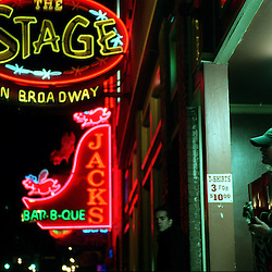 A street musician plays for tips in the shadows of the main stage on Broadway Avenue in Nashville, Tennessee. While many performers, and their fans, pack the bars on Music Row nearly every evening, street performers stake out the key locations nearby hoping to make some extra money.