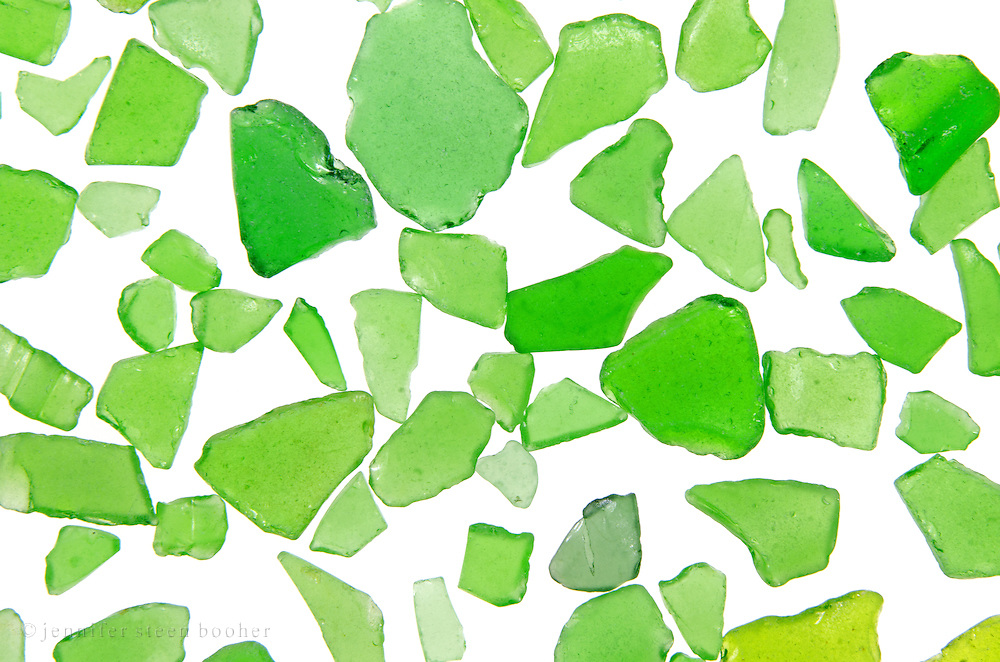 Detail of pile of green sea glass on light table.
