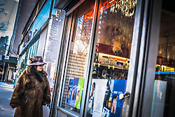 woman in a fur coat window shopping on the street in New York City