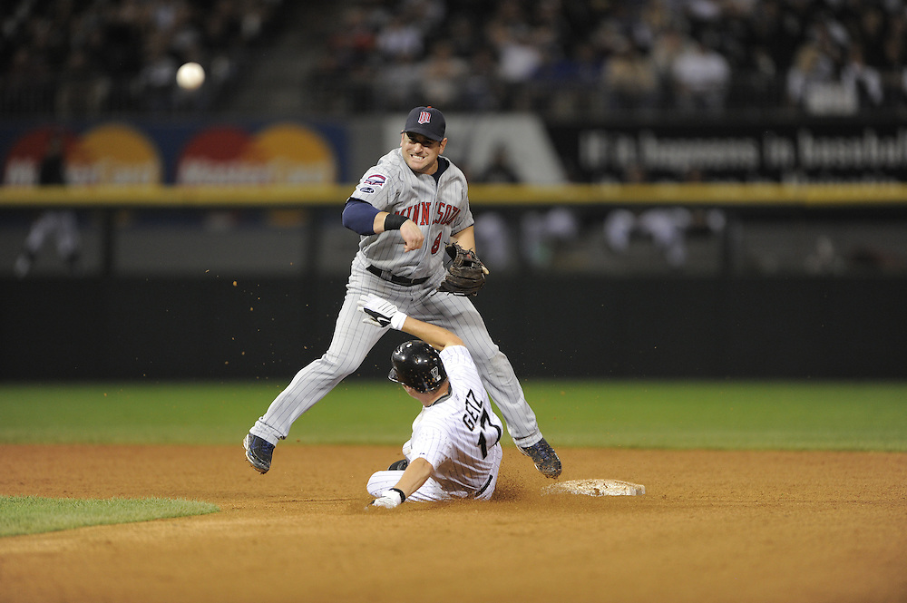 CHICAGO - SEPTEMBER 21:  Nick Punto #8 of the Minnesota Twins turns a double play over a sliding Chris Getz #17 of the Chicago White Sox on September 21, 2009 at U.S. Cellular Field in Chicago, Illinois.  The Twins defeated the White Sox 7-0.  (Photo by Ron Vesely)