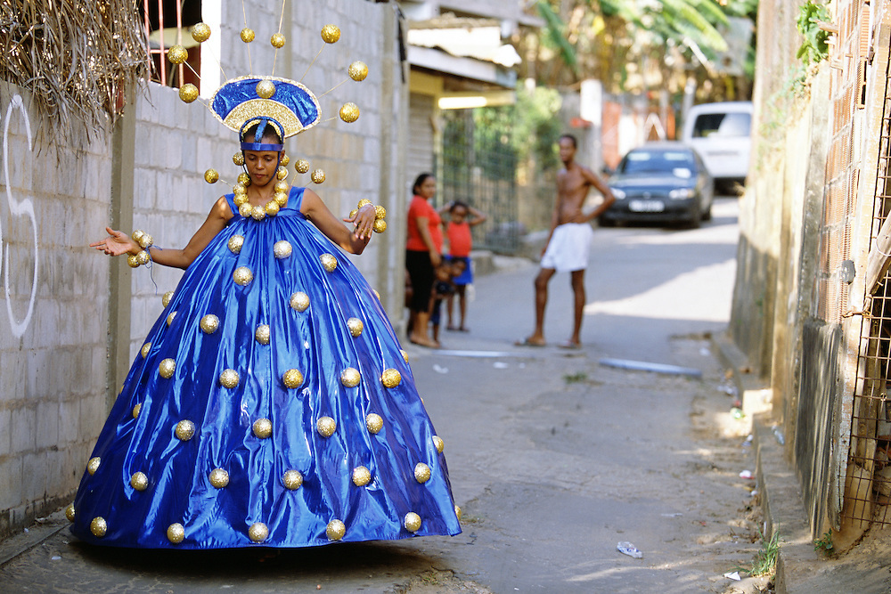 "Trinidad and Tobago ""MOKO JUMBIES: The Dancing Spirits of Trinidad"".(Outside the yard in Cocorite, Jasmine Girvan tries on the amazing Cheese Ball Queen costume designed by Laura Anderson Barbata. It will later be worn on stilts.).A photo essay about a stilt walking school in Cocorite, Trinidad..Dragon Glen de Souza founded the Keylemanjahro School of Art & Culture in 1986. The main purpose of the school is to keep children off the streets and away from drugs..He first taught dances like the Calypso, African dance and the jig with his former partner Cathy Ann Samuel.  Searching for other activities to engage the children in, he rediscovered the art of stilt-walking, a tradition known in West Africa as the Moko Jumbies , protectors of the villages and participants in religious ceremonies. The art was brought to Trinidad by the slave trade and soon forgotten..Today Dragon's school has over 100 members from age 4 and up..His 2 year old son Mutawakkil is probably the youngest Moko Jumbie ever. The stilts are made by Dragon and his students and can be as high as 12-15 feet. The children show their artistic talents mostly at the annual Carnival, which today is unthinkable without the presence of the Moko Jumbies. A band can have up to 80 children on stilts and they have won many of the prestigious prizes and trophies that are awarded by the National Carnival Commission. Designers like  Peter Minshall , Brian Mac Farlane and Laura Anderson Barbata create dazzling costumes for the school which are admired by thousands of  spectators. Besides stilt-walking the children learn the limbo dance, drumming, fire blowing and how to ride  unicycles..The school is situated in Cocorite, a suburb of Port of Spain, the capital of Trinidad and Tobago..all images © Stefan Falke"