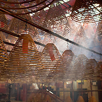 Asia, Peoples Republic of China, Hong Kong, Coils of incense slowly burn, sending up clouds of smoke inside Man Mo Temple on spring afternoon