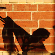 A toddler sitting in a stroller is silhouetted against a brick wall by the afternoon sun.