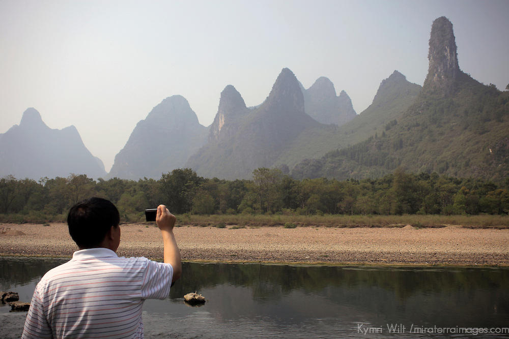 Asia, China, Guilin. Tourist captures scenery of karst formations on a Li River cruise.