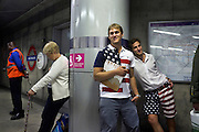 USA olympic team supporters wait for a train on London underground.