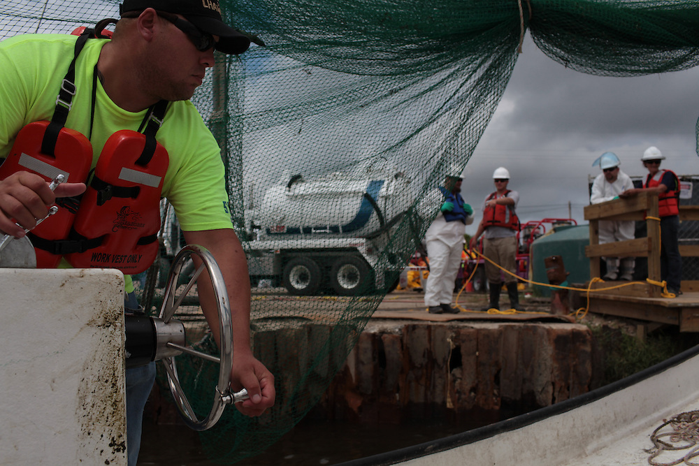 Eric Melerine bringing in contaminated hard boom to Hopedale, LA August 30, 2010.