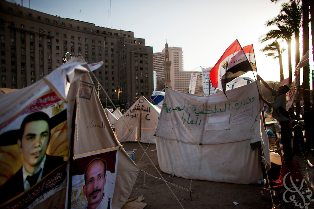 An Egyptian activist places Egyptian flags atop tents adorned with the images of Jan 25 revolution martyrs in Tahrir Square in Cairo, Egypt July 31,2011. Nearly six months after the Jan 25 revolution, many activists, families of martyrs and victims are still struggling to obtain justice and to fulfill the goals of the revolution. (Photo by Scott Nelson)