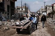 Iraq, Mosul: Civilians carry a dead body from new liberated area in west Mosul. Alessio Romenzi