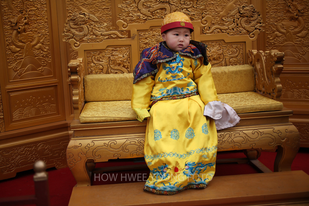 epa02585424 A Chinese boy dressed up in the costume of the Qing dynasty emperor poses for photos on a mock throne in Beijing, China 16 February 2011. While China's one child policy has produced many 'little emperors and empresses' by doting parents, the policy has been partly blamed for a rising number of child abductions as the traditional preference for a male heir to carry on the family name contributed to kidnappings by families desperate for boys, state media reported after a recent string of crack downs on children traffickers led by an online campaign.  EPA/HOW HWEE YOUNG