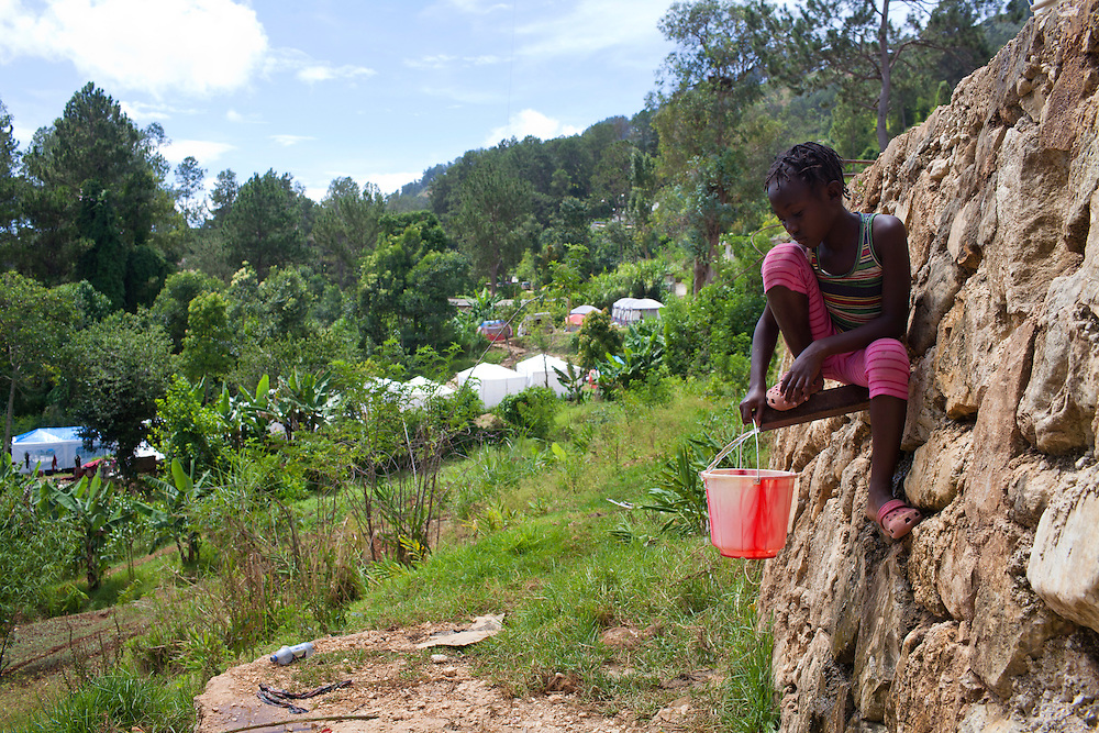 A girl gathers water from a pipe on July 17, 2010 in Kenscoff, Haiti.