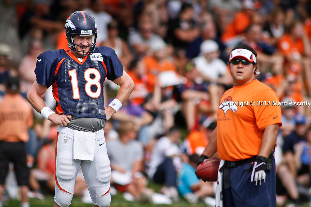SHOT 8/1/13 9:40:24 AM - Denver Broncos quarterback Peyton Manning #18 grimaces as he and the rest of the team run through drills during the team's training camp August 1, 2013 at Dove Valley in Englewood, Co.  (Photo by Marc Piscotty / © 2013)