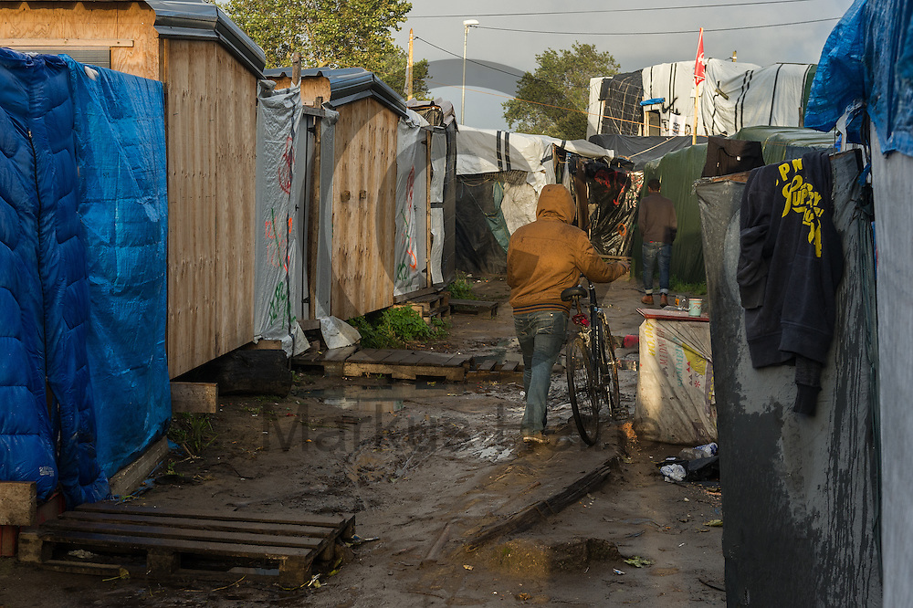 Calais, Frankreich - 17.10.2016<br /> Ein Migrant l&auml;uft im Dschungel von Calais auf einem Weg zwischen den H&uuml;tten. Das Fluechtlingscamp an der Kueste zum Aermelkanal soll laut franz&ouml;sischer Regierung in den n&auml;chsten Tagen geraeumt werden. In dem Camp leben um die 1000 Fluechtlinge und warten auf die Moeglichkeit zur Weiterreise durch den Eurotunnel nach Gro&szlig;britannien. Photo: Foto: Markus Heine / heineimaging<br /> <br /> Calais, France - 2016/10/17<br /> A Migrant walk in the Calais Jungle on a path between the huts. The refugee camp on the coast to the English Channel is to be cleared in the next few days, according to the French government. In the camp live around the 1000 refugees and wait for the possibility to travel further through the Eurotunnel to the UK. Photo: Foto: Markus Heine / heineimaging<br /> <br /> ------------------------------<br /> <br /> Ver&ouml;ffentlichung nur mit Fotografennennung, sowie gegen Honorar und Belegexemplar.<br /> <br /> Bankverbindung:<br /> IBAN: DE65660908000004437497<br /> BIC CODE: GENODE61BBB<br /> Badische Beamten Bank Karlsruhe<br /> <br /> USt-IdNr: DE291853306<br /> <br /> Please note:<br /> All rights reserved! Don't publish without copyright!<br /> <br /> Stand: 10.2016<br /> <br /> ------------------------------
