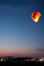 """Dawn Patrol 5"" - Photograph of a lit up hot air balloon flying over Reno during Dawn Patrol at the 2011 Great Reno Balloon Race."