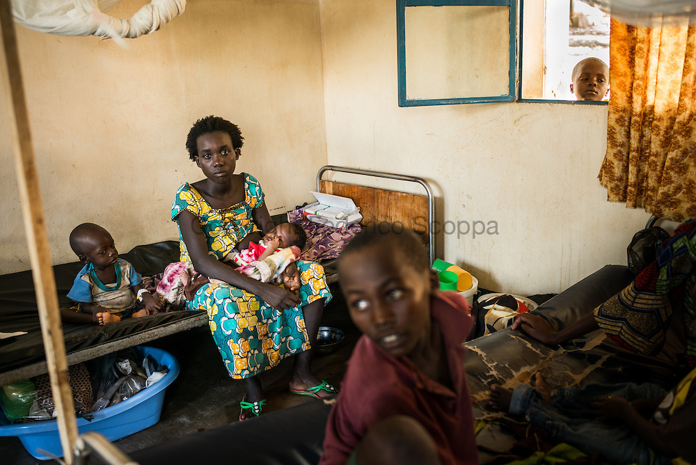 DRC / Burundi Refugees / 28-year old Alice seats on a hospital bed in DRC's South Kivu Province with two of<br /> her children aged 2 years and 3 weeks. Her 2-year old son suffers from malaria and<br /> malnutrition.<br /> <br /> Alice is one of the nearly 8,000 Burundian refugees who have fled to the DRC over<br /> the past few weeks. She fled while she was already 9-month pregnant and gave birth<br /> to a baby girl just four days after her arrival in the DRC. She walked 24 hours with<br /> her husband and their four children, an entire day and an entire night, to reach DRC<br /> without eating. She says that it was very difficult. <br /> <br /> 7,661 Burundians refugees have crossed into the DRC over the past few weeks. The new<br /> arrivals are being hosted by local families, but the growing numbers are straining<br /> available support. UNHCR is helping some 500 vulnerable refugees at a transit centre<br /> at Kavimvira and in another centre at Sange. Work is ongoing to identify a site<br /> where all the refugees can be moved, and from where they can have access to<br /> facilities such as schools, health centers and with proper security./ UNHCR / F.Scoppa / May 2015