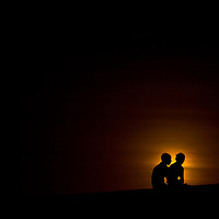 Lovers sit on the fortress wall during sunset in Cartagena, Colombia...Photo by Robert Caplin.