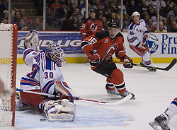 Feb 20, 2007; East Rutherford, NJ, USA; New Jersey Devils forward Sergei Brylin (18) watches as Brian Rafalski's shot slides past New York Rangers goalie Henrik Lundqvist (30) during the first period at Continental Airlines Arena in East Rutherford, NJ.