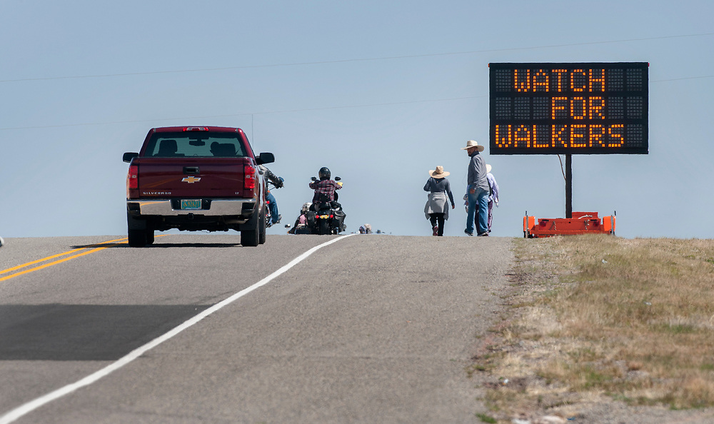 em041317b/jnorth/People walk along Highway 503 through Nambe on their way to the Santuario de Chimayo Thursday April 13, 2017. Hundreds of people were making their pilgrimage to the Northern New Mexico church on Thursday, thousands will on Good Friday. Law enforcement and emergency assistance are set up all along the roads leading to Chimayo.  (Eddie Moore/Albuquerque Journal