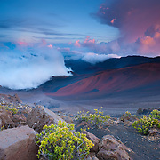 Storm clouds climb up the crater in Haleakala National Park on the Hawaiian island of Maui at sunset.