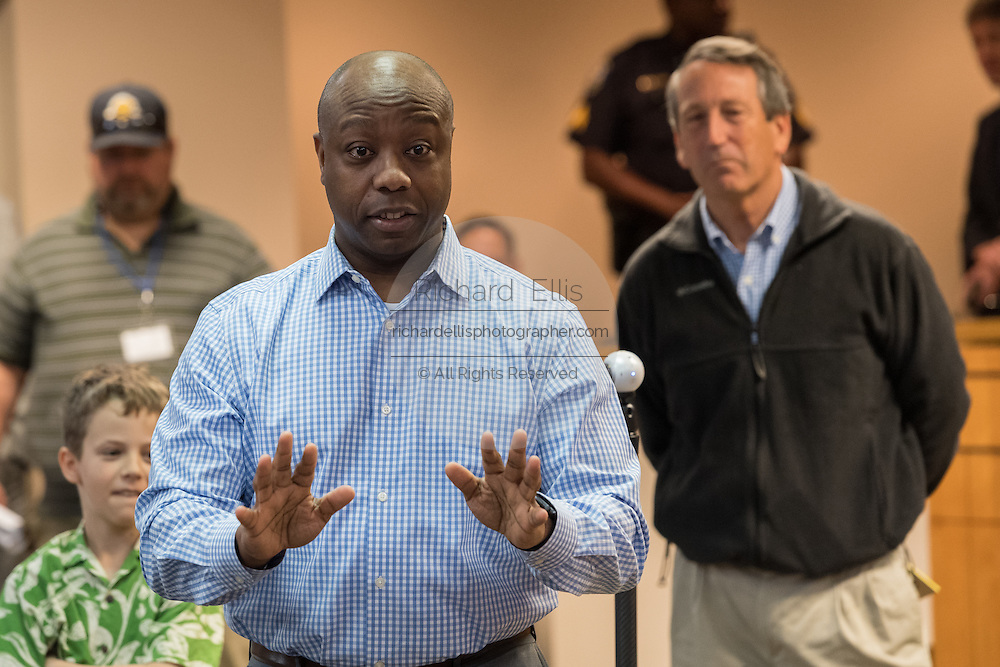 U.S. Sen. Tim Scott answers a question with an angry constituent as Rep. Mark Sanford look on, right, at a town hall meeting February 18, 2017 in Mount Pleasant, South Carolina. Hundreds of concerned residents turned up for the meeting to address their opposition to President Donald Trump during a vocal meeting held by U.S. Rep. Mark Sanford and Senator Scott.