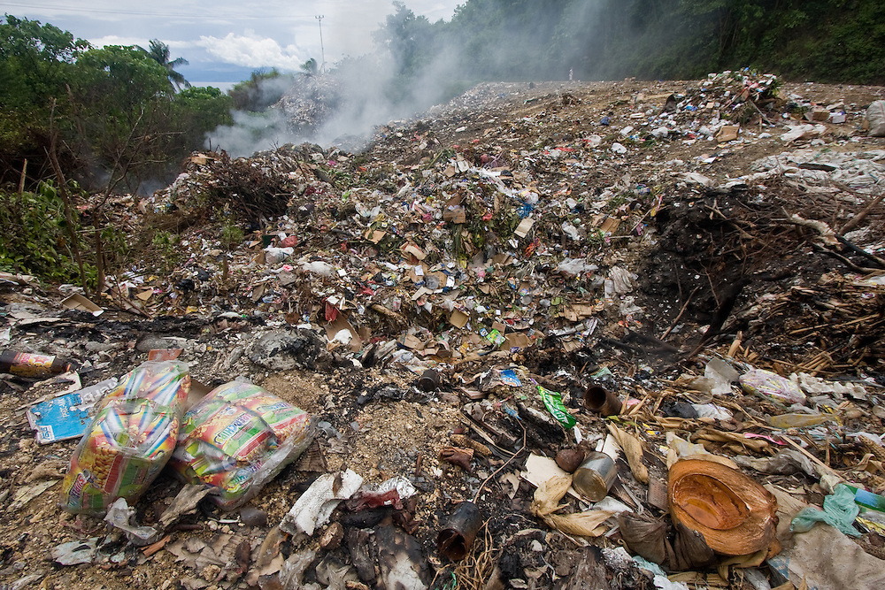 Piles of trash smolder by the side of the road in Central Sulawesi