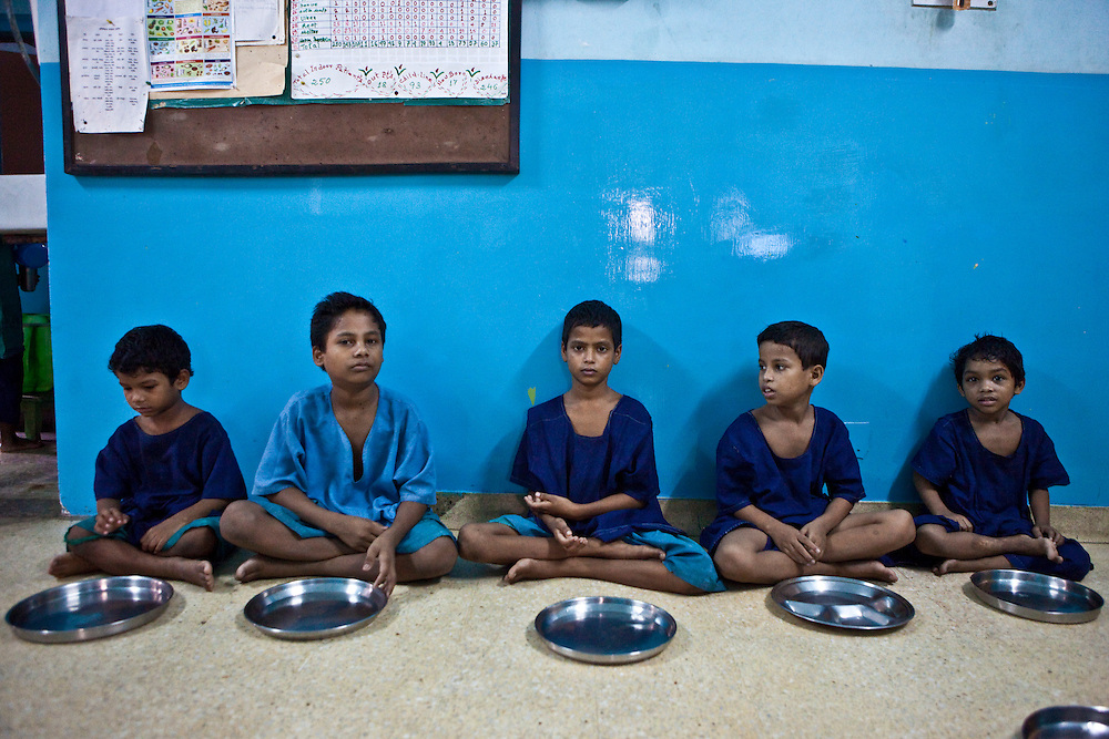 Five boys wait for their food at the CINI halfway house in Calcutta, India..Child In Need Institute (CINI) run halfway houses for vulnerable street children from as young as 5 years old with the aim of reconnecting the children with their families.