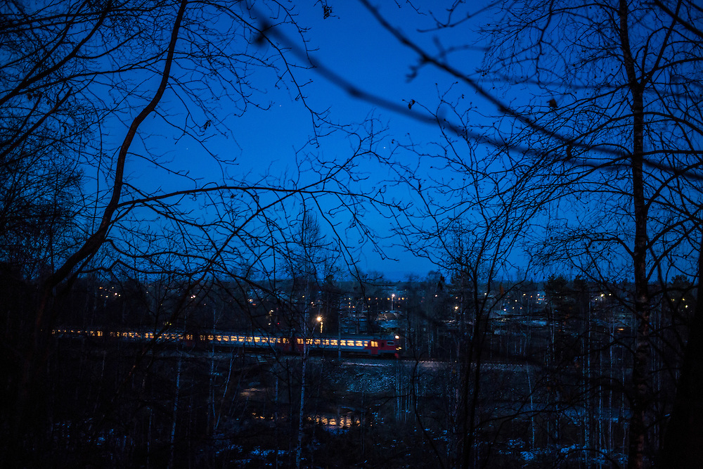 A passenger train passes by town at dusk on Monday, October 28, 2013 in Baikalsk, Russia.
