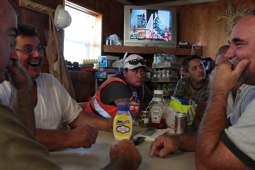 Local fishermen watching Katrina anniversary footage in Serigne's cafe on August 25th, 2010. The local fishermen were working for BP, helping clean up the Deepwater Horizon Oil Spill.