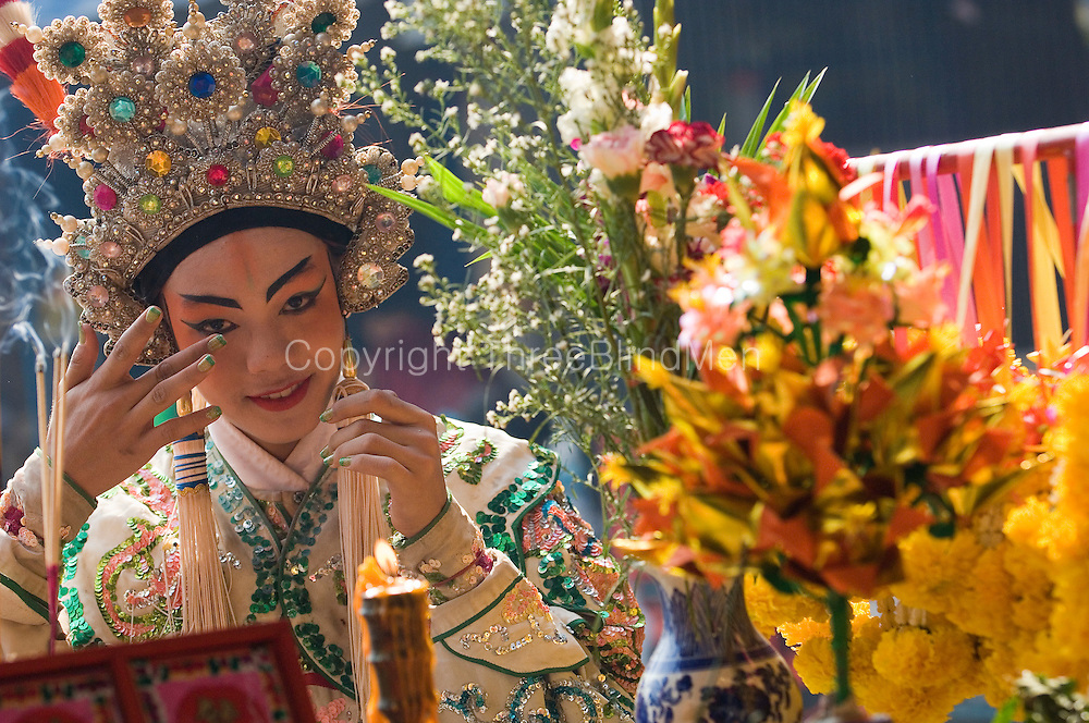 Chinese religious festival in a small town. Particpants in theatre in costume at a shrine in the town.