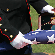 A marine holds a photo of fallen comrade Sgt. Jon Bonnell, along with the flag that was presented to his family at his funeral in Ft. Dodge in August of 2007.