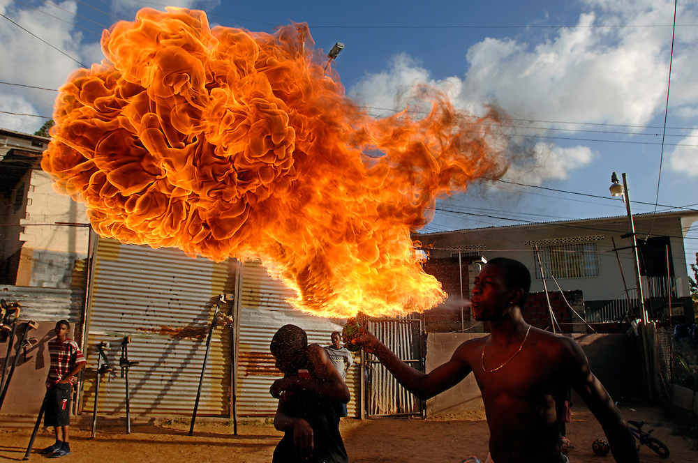 "A member of the Keylemanjahro School of Arts and Culture in Cocorite, Trinidad, practices his fire blowing skills...Prints available in 3 sizes:.20""x30""   90.00 $ .24""x36"" 150.00 $.30""x40"" 180.00 $.personal download: 45 $ and 90 $. .Click 'buy print' and choose your size...Different sizes or comments: stefanfalke@mac.com"