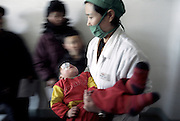 North Korea Eye Surgery Workshop. O Se Bok (6) is carried from surgery by a North Korean nurse after his cataract operation.