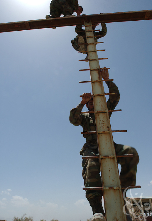 Afghan National Army (ANA) soldiers navigate a U.S. Army Special Forces obstacle course  during a training competition May 27, 2002 at an Afghan National Army (ANA) training facility in Kabul, Afghanistan. Special Forces units conduct ten week training courses for the Afghan Army in the hope that a better trained military will mean a more stable Afghanistan.