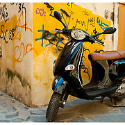 Black scooter and yellow wall with graffiti. Chania, Crete, Greece.