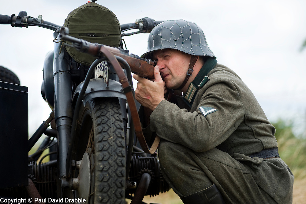 A re-enactor from the Northern World War Two Association Living History group, portraying a Gefreiter of the Panzer-Grenadier-Division Grossdeutschland, takes a firing position with his Mauser K98 rifle behind a BMW R71 motorcycle and sidecar during a large scale battle re-enactment..<br /> SPAM 1940's Weekend. Heckmonwyke near Wakefield 10 July 2010 <br /> Images &copy; Paul David Drabble