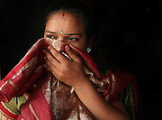 Surekha Kamble covers her nose and mouth in reaction to a bad small in Miraj's redlight district where ives and works as a Devadasi sexworker. Kamble has been a Devadasi sexworker since she was sixteen. Her mother was a Devadasi sexworker and as is tradition, she and her sister too became Devadasis.  She is also a peer educator involved in raising awareness in her community about HIV/AIDS as well as other sexually transmitted diseases.  Her two daughters, Chandrike and Ropani, are both being educated at a residential school for the children of Devadasis and she has hopes that they will not follow her into the Devadasi lifestyle.