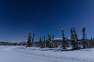 A moonlit night sky over Clunie Lake and the Chugach Mountains in Southcentral Alaska. Winter.