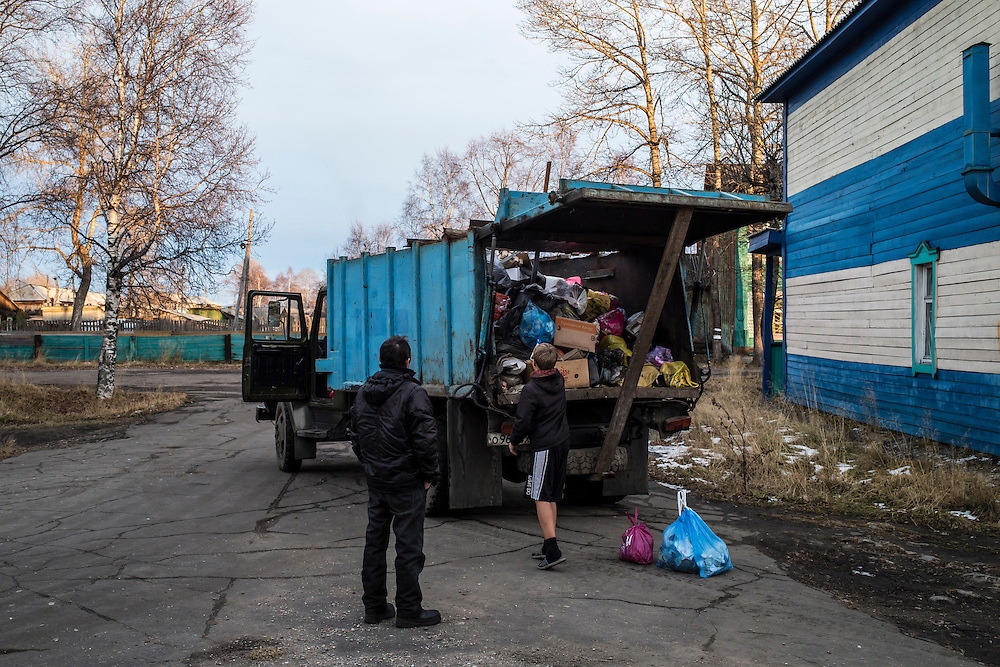 A boy tosses trash in the back of a garbage truck on Wednesday, October 23, 2013 in Vydrino, Russia.