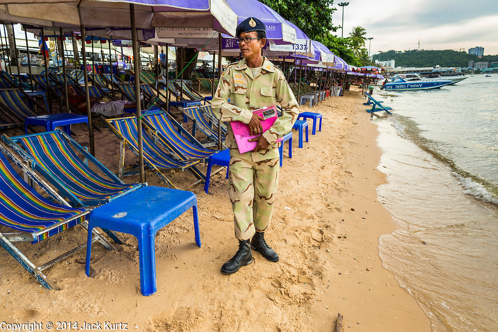 "26 SEPTEMBER 2014 - PATTAYA, CHONBURI, THAILAND: A defense volunteer checks on a business that rents beach umbrellas to tourists in Pataya. Pataya, a beach resort about two hours from Bangkok, has wrestled with a reputation of having a high crime rate and being a haven for sex tourism. After the coup in May, the military government cracked down on other Thai beach resorts, notably Phuket and Hua Hin, putting military officers in charge of law enforcement and cleaning up unlicensed businesses that encroached on beaches. Pattaya city officials have launched their own crackdown and clean up in order to prevent a military crackdown. City officials have vowed to remake Pattaya as a ""family friendly"" destination. City police and tourist police now patrol ""Walking Street,"" Pattaya's notorious red light district, and officials are cracking down on unlicensed businesses on the beach.     PHOTO BY JACK KURTZ"