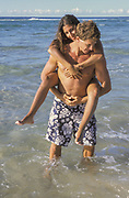 Australia, Queensland, N. Stradbroke Island, man giving woman a piggyback ride on beach.  MR available