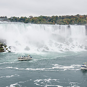 """The """"Maid of the Mist"""" boats tour beneath American Falls and Bridal Veil Falls. The town of Niagara Falls in Ontario, Canada, gives excellent views of all three sections of Niagara Falls, which drops 167 feet (51 m). Niagara Falls has the highest flow rate of any waterfall in the world. Niagara Falls is the name for the combined flow of Horseshoe Falls, American Falls and Bridal Veil Falls, on the Niagara River along the international border between Ontario, Canada and New York, USA. The Niagara River drains Lake Erie into Lake Ontario. Horseshoe Falls is the most powerful waterfall in North America, as measured by vertical height combined with flow rate. The falls are 17 miles north-northwest of Buffalo, New York and 75 miles south-southeast of Toronto."""