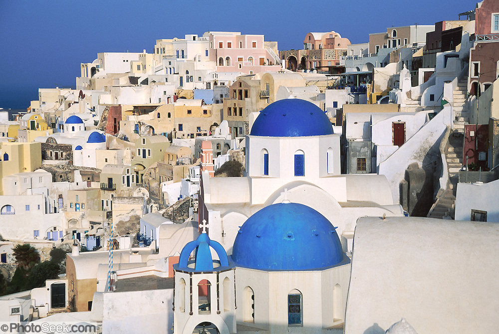 Bell towers and blue-domed Greek Orthodox Churches grace the village of Oia on Santorini Island, an ancient volcanic caldera rim in the Aegean Sea, in Greece, Europe. After major destruction in a 1956 earthquate, Oia town was rebuilt as a multi level maze of fascinating whitewashed architecture.