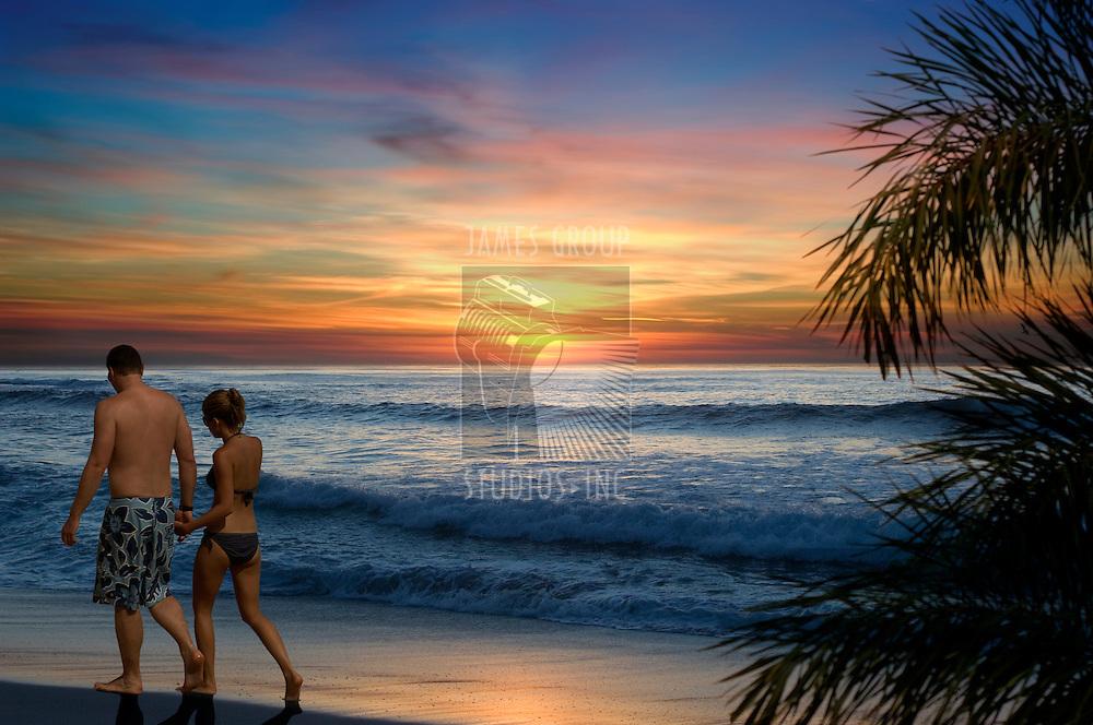 Couple walking along a tropical beach at sunset