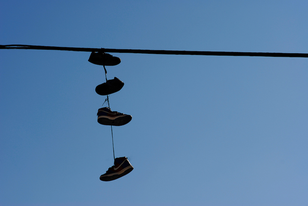 Shoes hanging in street. NYC.