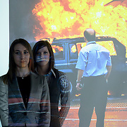 Two female BAA security instructors stand in front of a Powerpoint image showing the Glasgow airport terrorist attack.