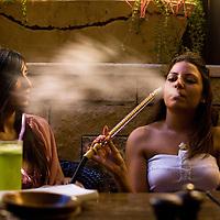 Deux jeunes Palestiniennes fumment un narguile dans le lounge bar et restaurant Italien du nom de Orjuwan le 01 Octobre 2010 a Ramallah...Credit photo: Olivier Fitoussi.