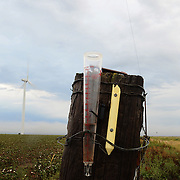 A rain gauge wired to a fencepost is partially filled after a couple of brief showers in the Texas panhandle north of Amarillo.<br />