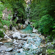 Walk a trail and hikers' suspension bridge along Tolminka river gorge, starting at the parking lot at the Triglavski narodni park (TNP) sign, near Zatolmin, Julian Alps, Slovenia, Europe. Loop upwards to the scenic Devil's Bridge (Hudicev most, built 1907, seen at top of photo), which carries the Tolmin-Cadrg automobile road sixty meters above Tolminka River. Tolmin gorges (Tolminska korita) are among the longest and deepest gorges in Slovenia and are the lowest point (180 meters elevation) in Triglav National Park (TNP). Panorama stitched from 6 overlapping photos.