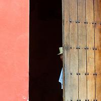 Cartagena , Colombia - December 21 2010 : Doorman looking from the front door of an apartapent building